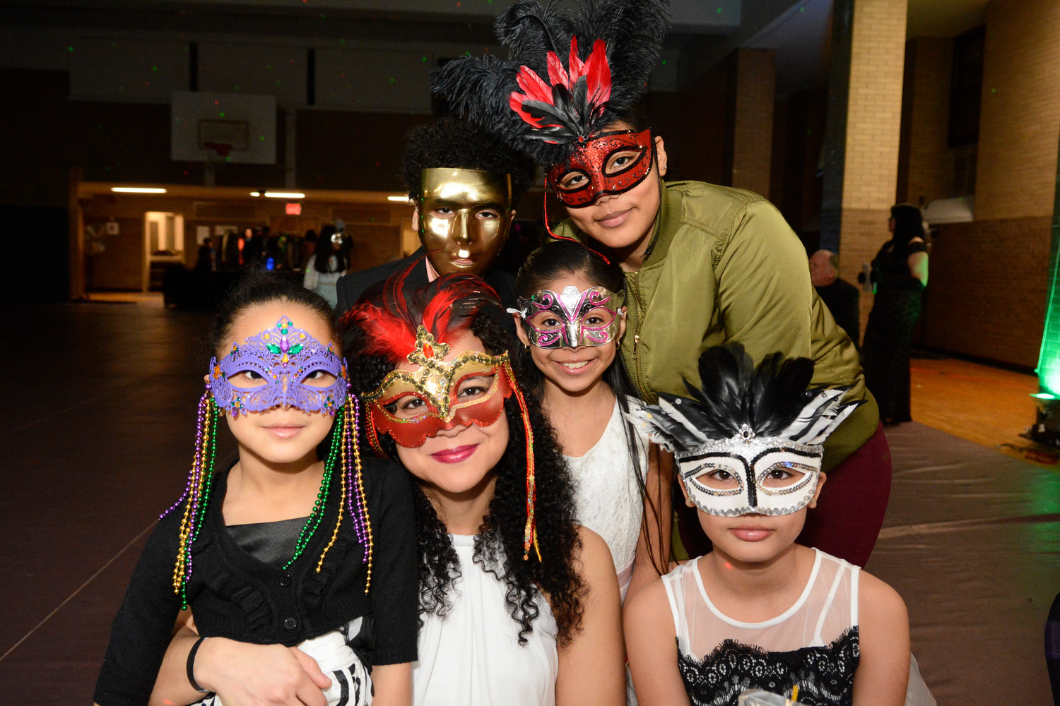 Yoely Peralta poses with daughters Alanna, age 6, in purple mask, and Alyssa, 10, in black and white mask, and behind her, son Andrew, 12, in gold mask and daughter Ariana, 15, in red mask and olive shirt. Between Ms. Peralta and Ariana is family friend Alina Morales, 9, in silver and pink mask.
