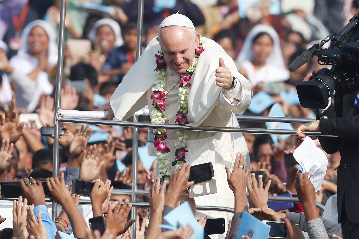 Pope Francis gives a thumbs up as he greets the crowd before celebrating Mass and the ordination of priests in Suhrawardy Udyan park in Dhaka, Bangladesh, Dec. 1, 2017.