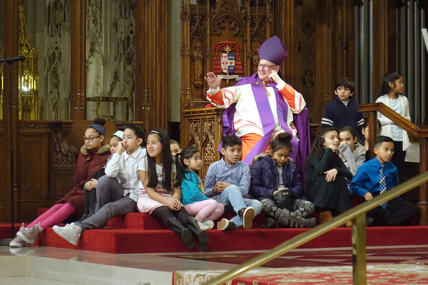 During the signings by catechumens, children from the congregation gather near Cardinal Dolan, the principal celebrant, in the sanctuary. This year's Rite of Election drew 305 catechumens from 81 parishes.