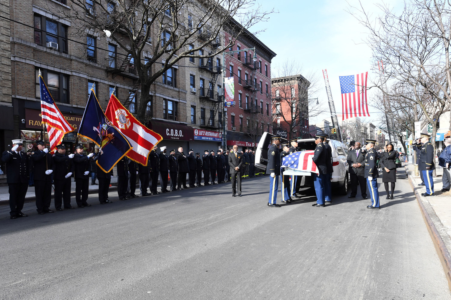 U.S. Army and FDNY members salute Mensah's casket outside the church.