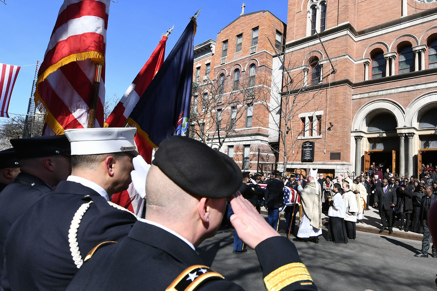U.S. Army and FDNY members salute as Cardinal Dolan blesses Mensah's casket outside the church after the liturgy.
