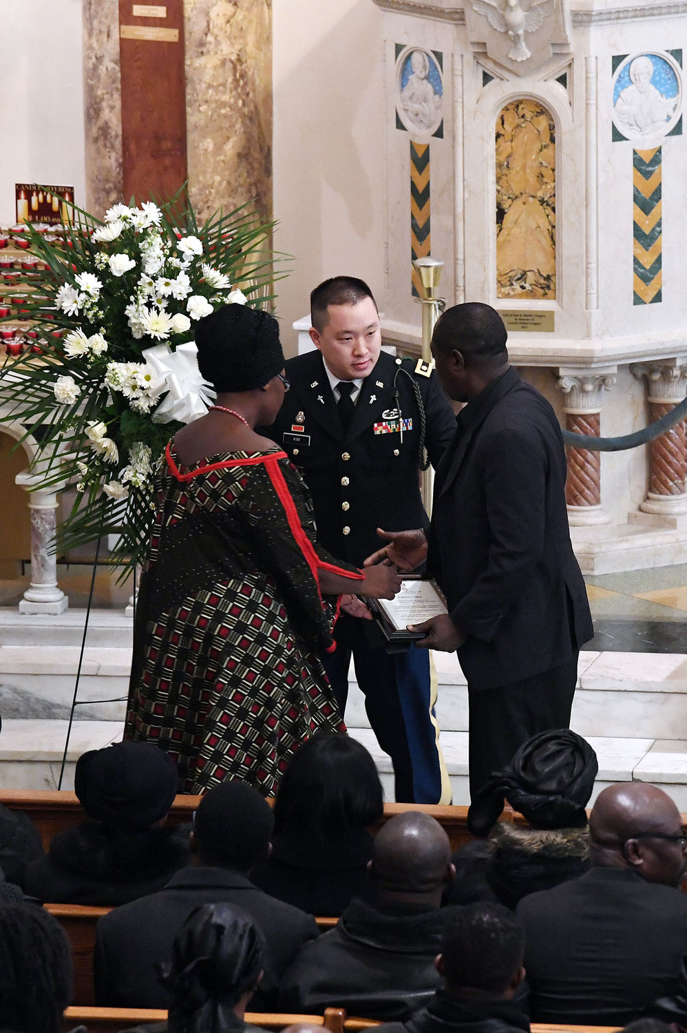 Army Maj. James Kim, a chaplain, top right, speaks with the fallen soldier's father, Kwabena Mensah, after a certificate was presented to him.