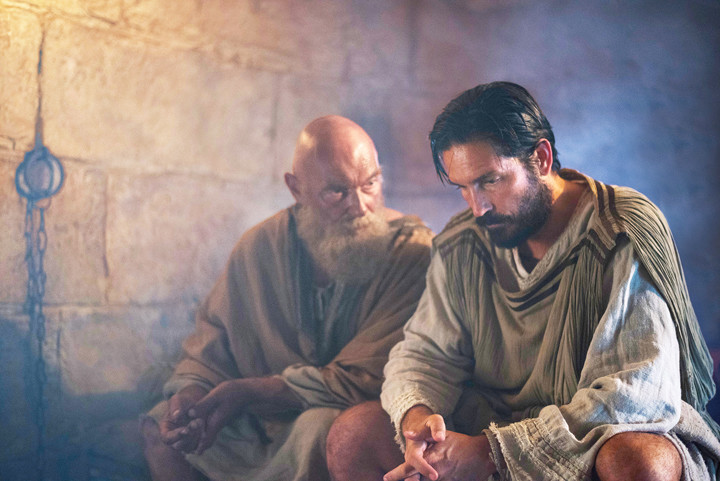 "IN PRISON—Jim Caviezel as Luke and James Faulkner as Paul are seen in the film ""Paul, Apostle of Christ."""