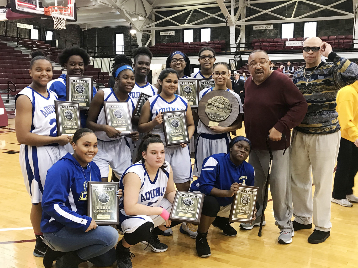 Aquinas High School girls' basketball players hold their individual and team championship plaques after winning a second consecutive CHSAA B state championship with a 69-43 victory over St. Dominic at Fordham University March 10. The Lady Bears will compete in the state federation tournament in Glens Falls March 23-25.