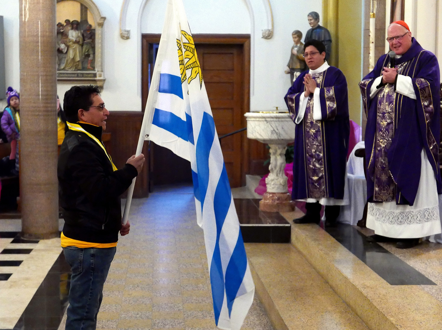 A flag is carried to the main altar.