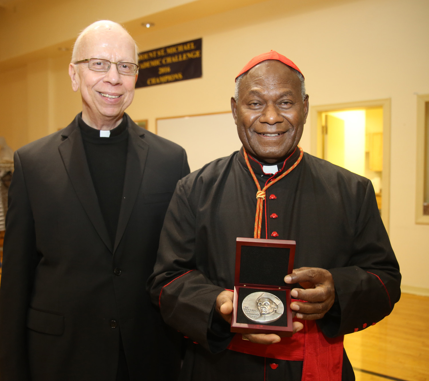 Cardinal Ribat displays the Loyola Medal after Mass with Father Dennis Yesalonia, S.J., the pastor of St. Ignatius Loyola.