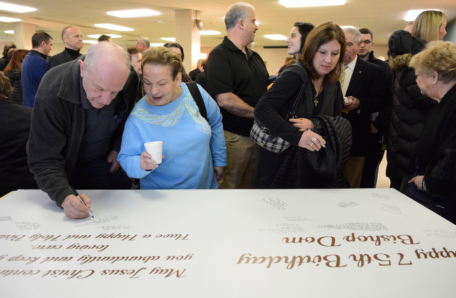 Well-wishers sign an oversized birthday card for the bishop.