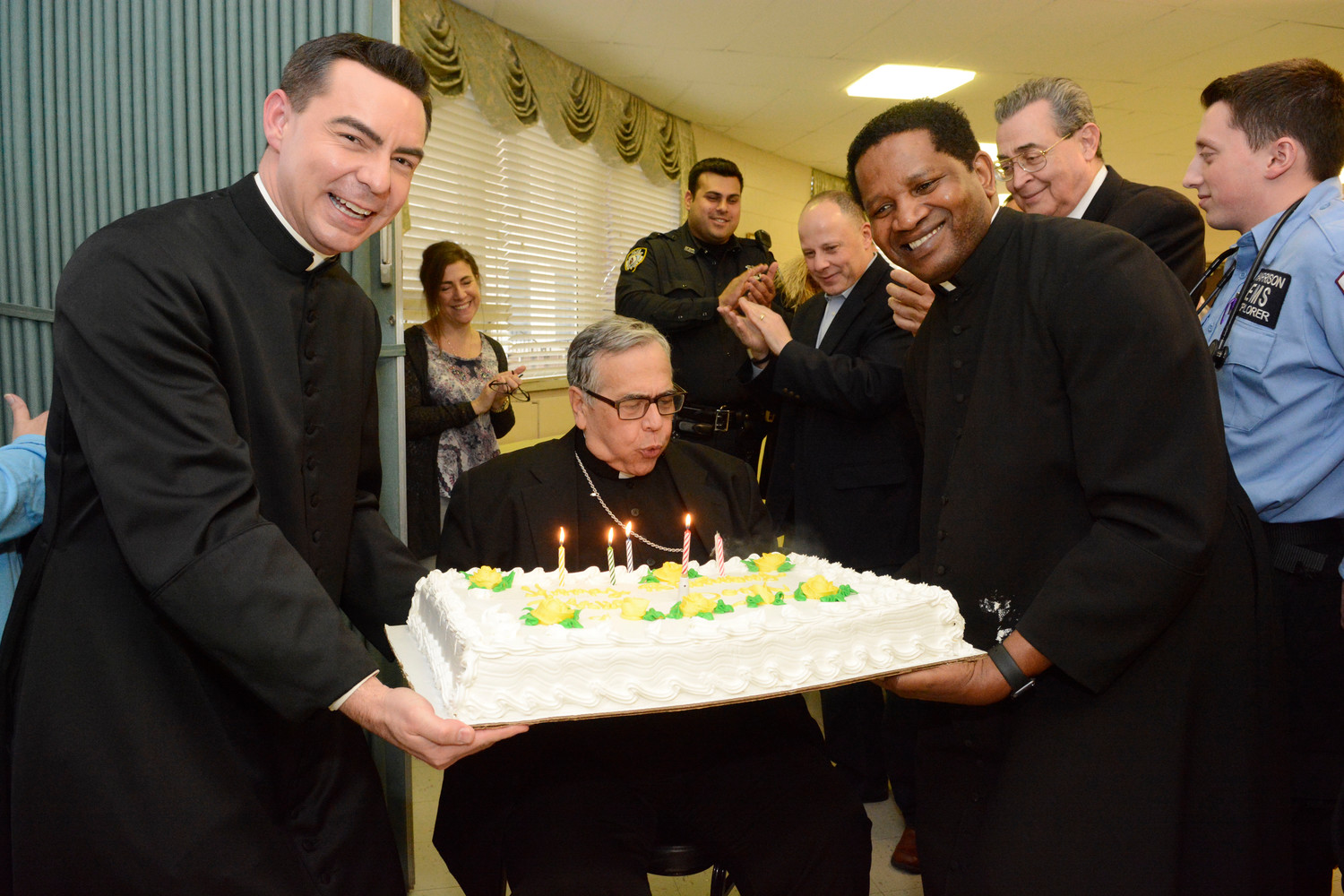 Bishop Lagonegro blows out the candles on his birthday cake at the party in the parish hall after the liturgy. Holding the cake at his left is Father Monturo and, at right, is Father George Kanshamba, a parochial vicar at St. Anthony's. Behind Father Kanshamba is Richard Morgado, a cousin of Bishop Lagonegro who was a lector at the Mass.