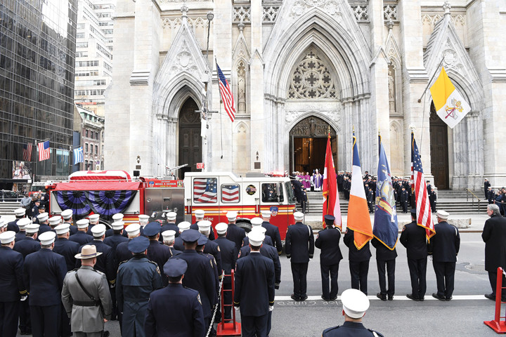 FALLEN HERO—A fire truck from Engine 69 in Harlem arrives at St. Patrick's Cathedral with the casket of Lieutenant Michael R. Davidson before the start of the Funeral Mass celebrated by Cardinal Dolan March 27. Lt. Davidson died battling a fire in Harlem with firefighters from Engine 69 March 23.