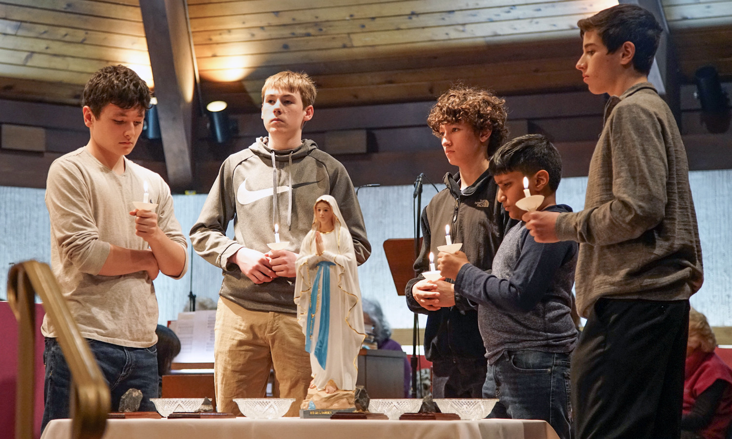 Youths surround statue of Our Lady during the Rosary by Candlelight. From left, they are Adam Dingman, James Dingman, Brendan Mackin, Abel Abraham and Tyler Nicholson.