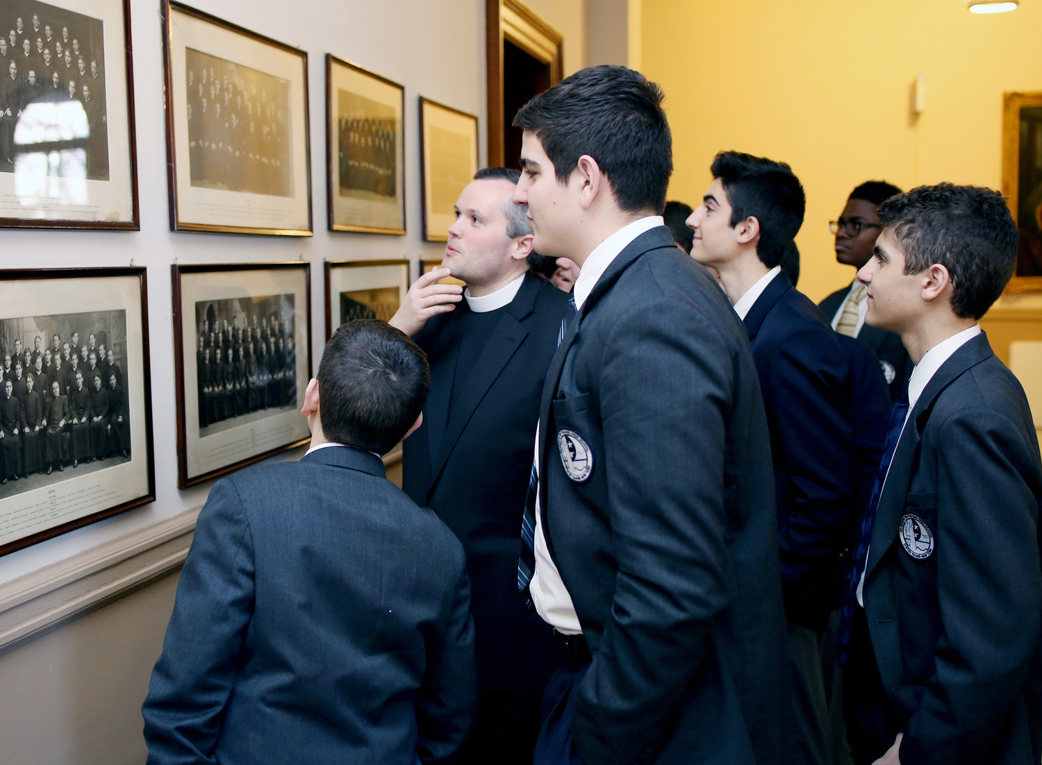 Father John McCarthy looks at photos of ordination classes at St. Joseph's Seminary with students from St. Joseph by-the-Sea High School on Staten Island, where he serves as chaplain.