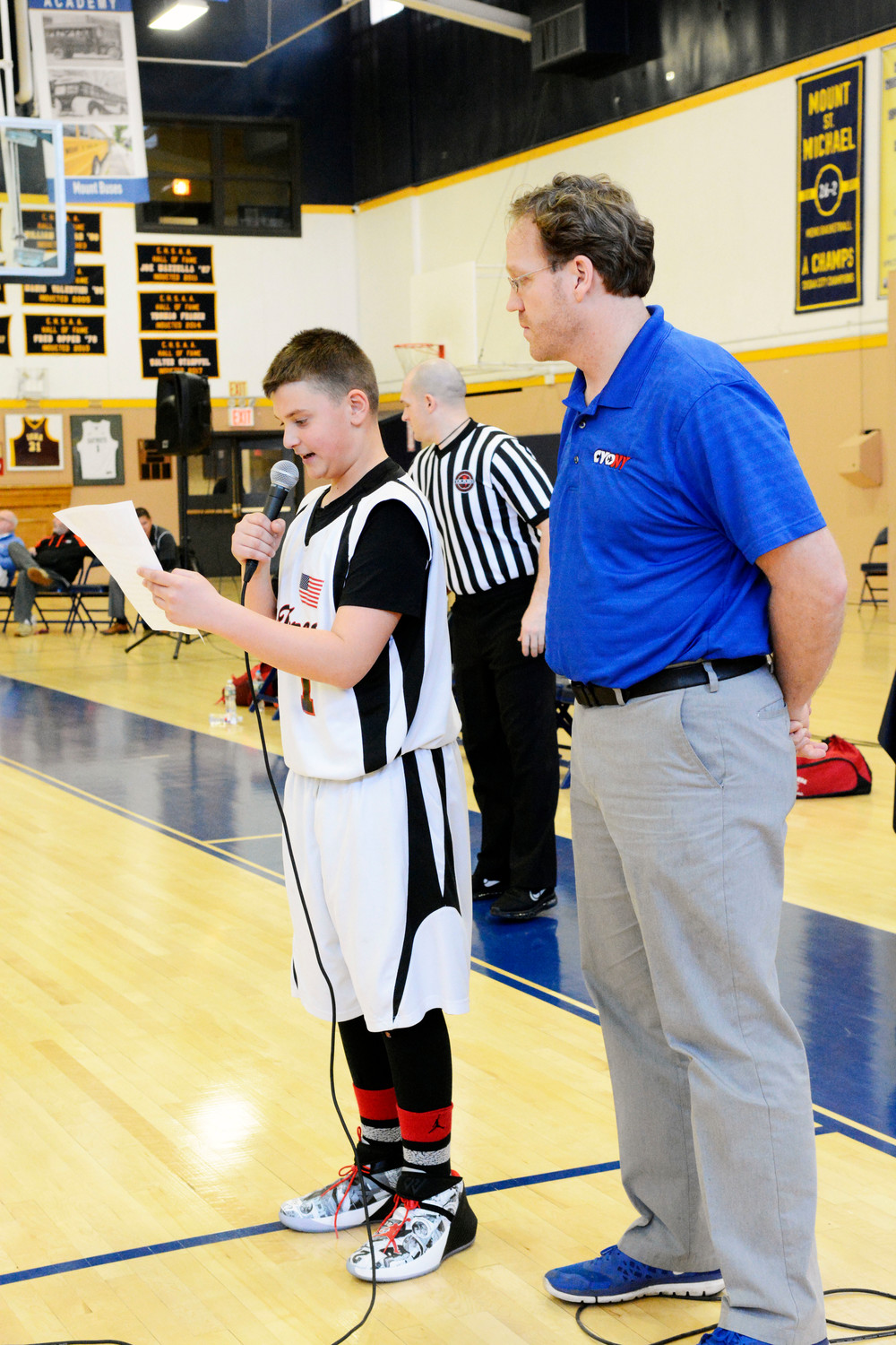 St. Teresa's Dom DiFiore reads the CYO Pledge of Sportsmanship at the sixth-grade boys championship game. With him is Seth Peluso, CYO's director of operations.