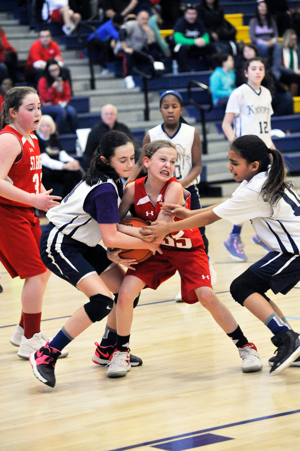Riley Harold of St. Gregory Barbarigo, Garnerville, center, battles Julian Cinquina, left, and Sofia Tavarez, right, both of St. Columbanus, Cortlandt Manor, in the archdiocesan CYO fifth-grade girls' championship game at Mount St. Michael Academy in the Bronx March 17. St. Columbanus won 19-15.