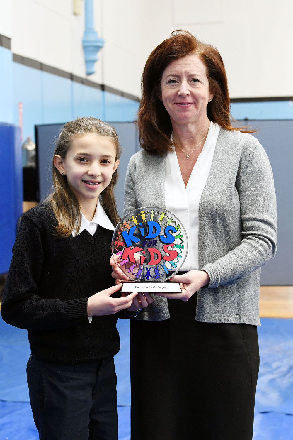 Seventh-grader Sofia Biondi presents the Kids for Kids thank you gift to school principal Tara Hynes.