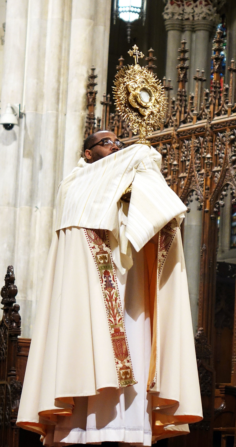 Deacon Kareem Smith, a transitional deacon stationed at St. Patrick's Cathedral, lifts a monstrance containing the Blessed Sacrament before a Vigil Mass celebrated by the cathedral rector, Msgr. Robert Ritchie, not pictured.