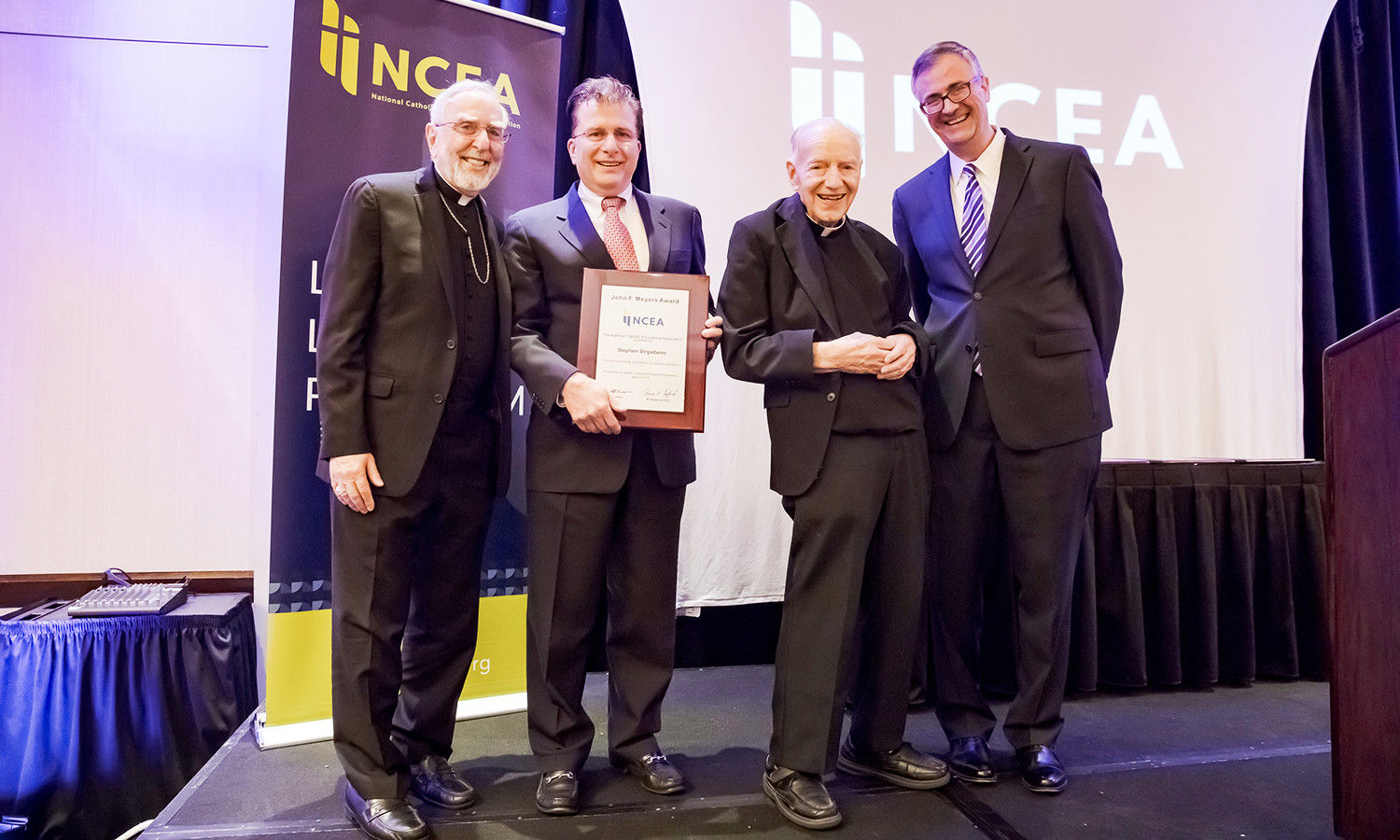 NCEA Board Chair Bishop Gerald Kicanas, far left; honoree Steven Virgadamo, associate superintendent for leadership formation for the archdiocese; Msgr. John F. Meyers, the namesake of Virgadamo's award; and NCEA President/CEO Dr. Thomas Burnford smile broadly after Virgadamo was recognized at an awards banquet April 2 at the National Catholic Educational Convention & Expo in Cincinnati.