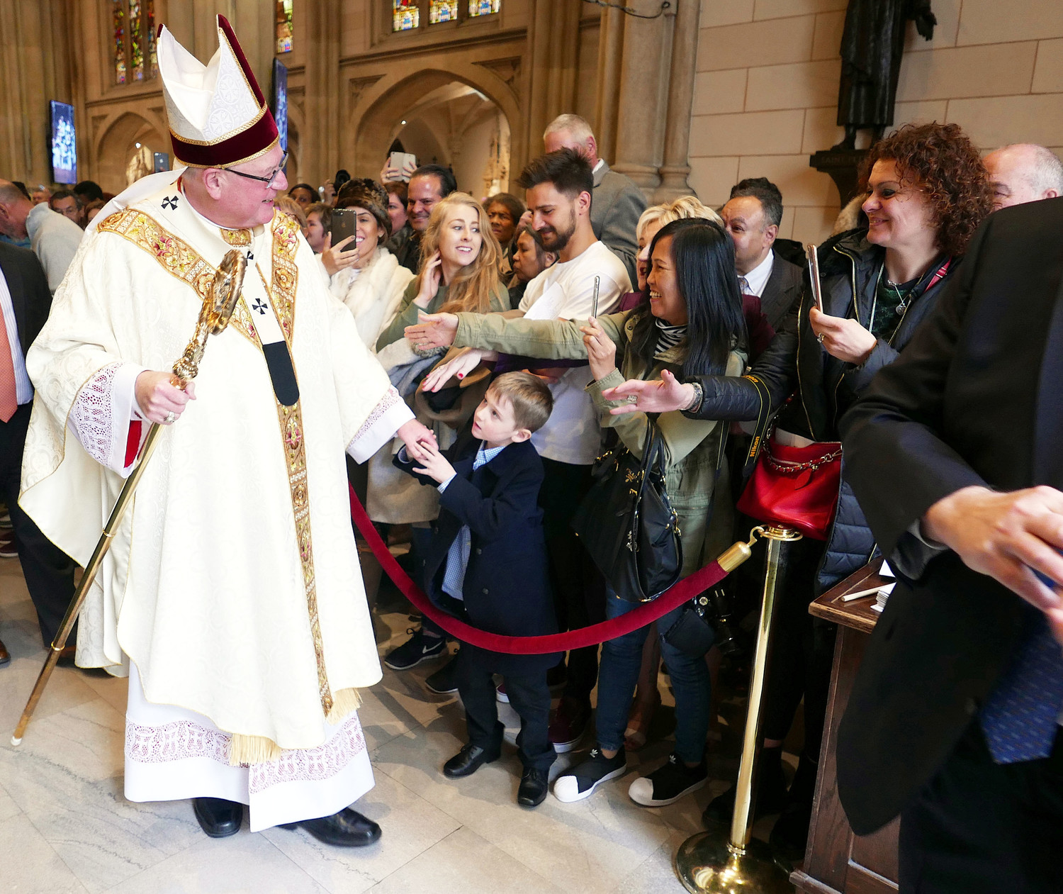 "Cardinal Dolan greets Mass-goers inside St. Patrick's Cathedral. The cardinal celebrated the 10:15 a.m. Mass on Easter Sunday, April 1, before a congregation of 2,000. Speaking with the press afterward, the cardinal expressed gratitude for the vast number gathered. ""Thank God they're here,"" he said. ""I hope they come back."""