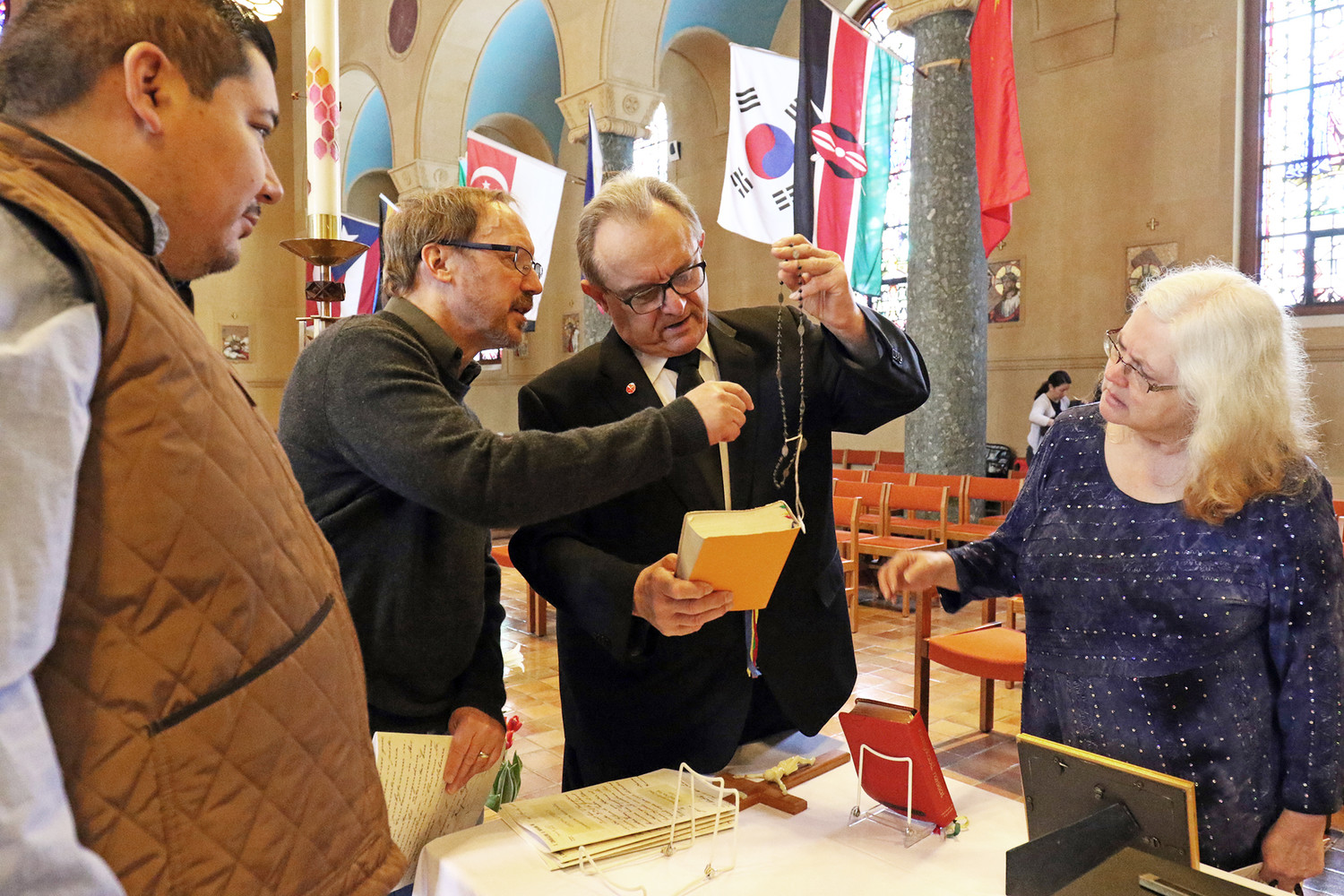 Jose Velazquez, left, Greg Darr, Brother John Blazo, M.M., and Lori Alpert look at a display of historical items after attending the Mass. The liturgy marked the opening of a yearlong celebration by the Maryknoll Society of the centennial of its first mission sending.