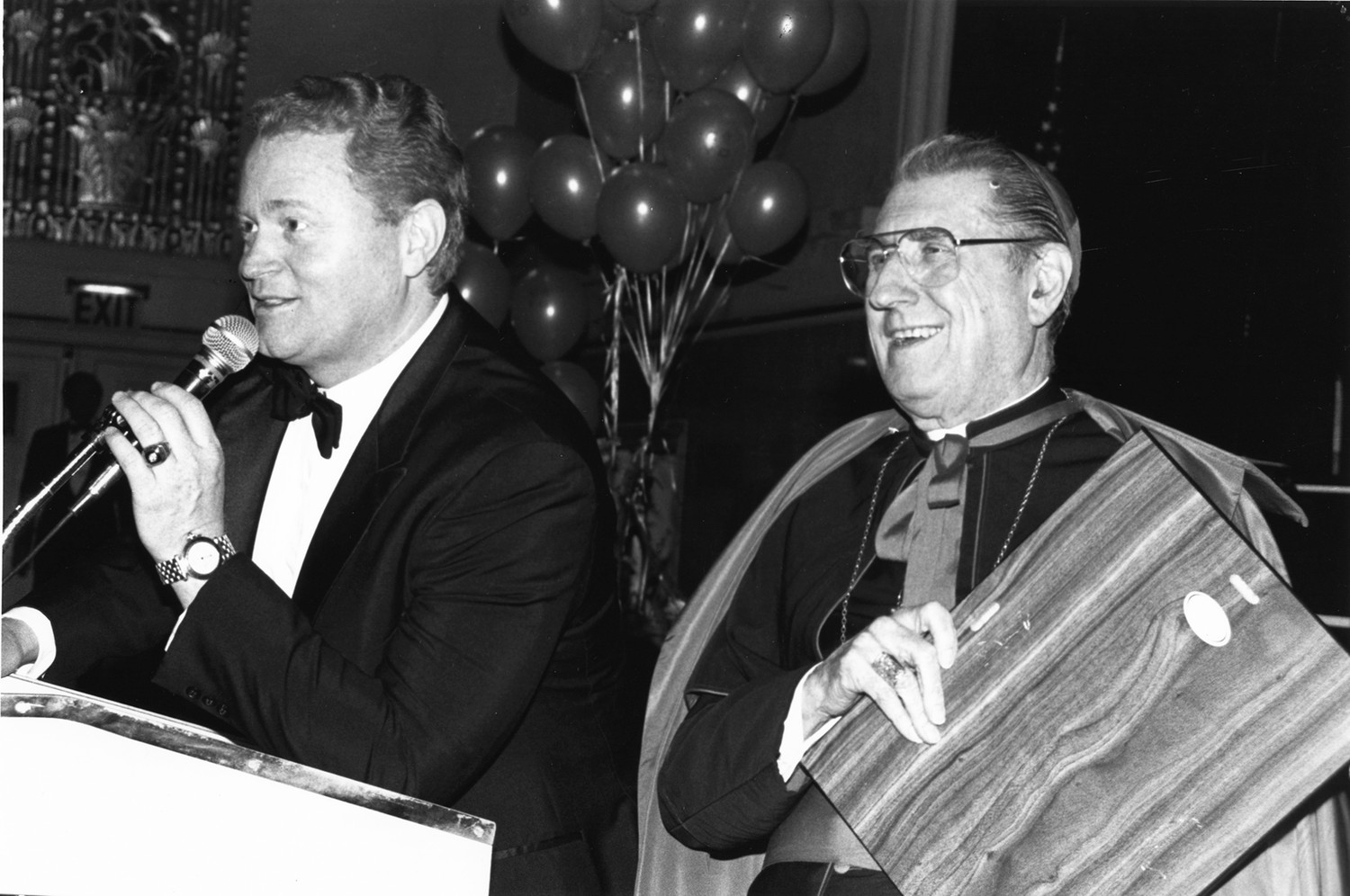 Rusty Staub joins Cardinal John O'Connor at the 1989 CYO Club of Champions Tribute Dinner honoring his former New York Mets teammate Gary Carter. At the time, Staub was a television announcer for the Mets.