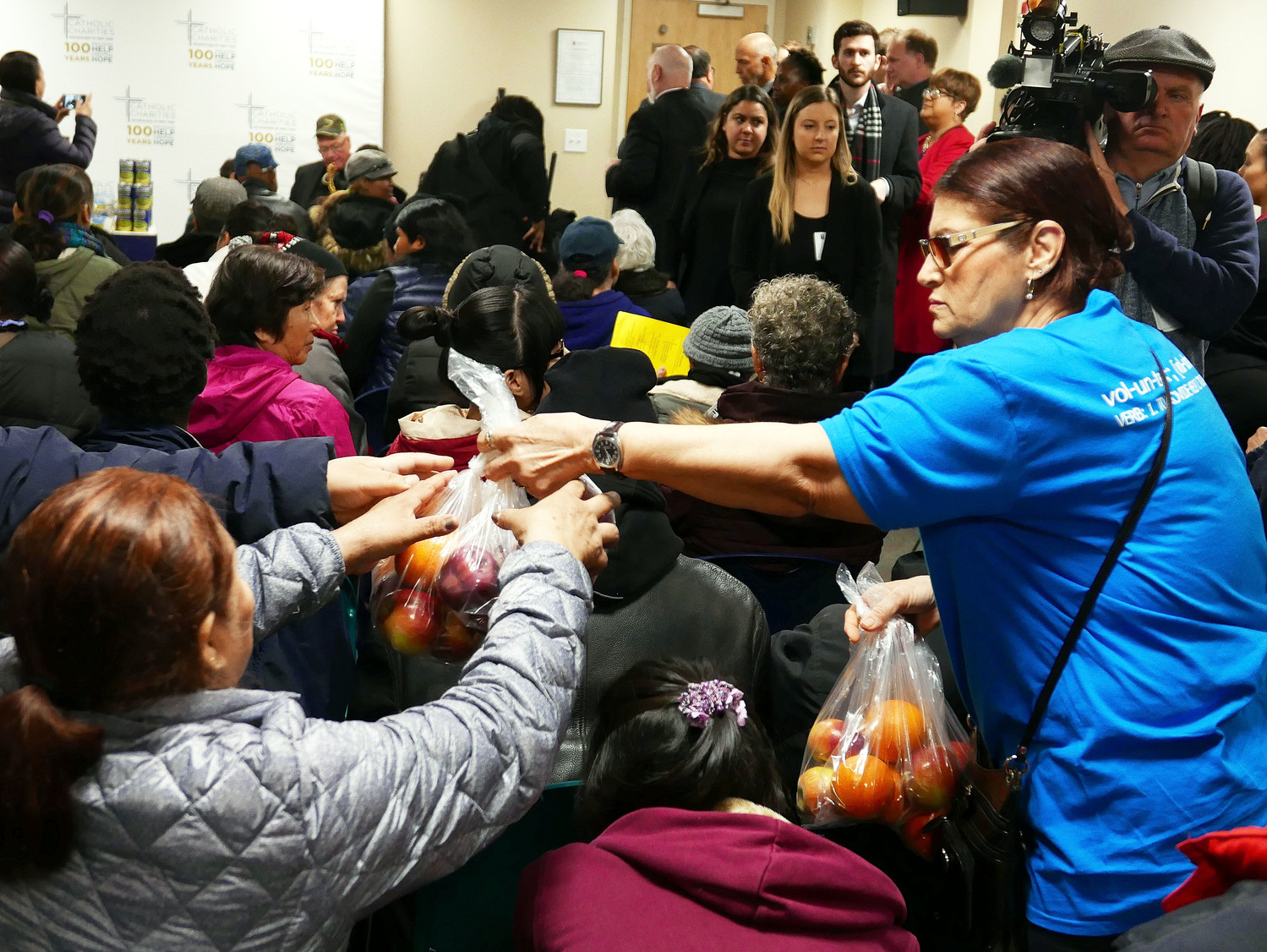 A volunteer hands out a bag of apples at Cristo Rey.