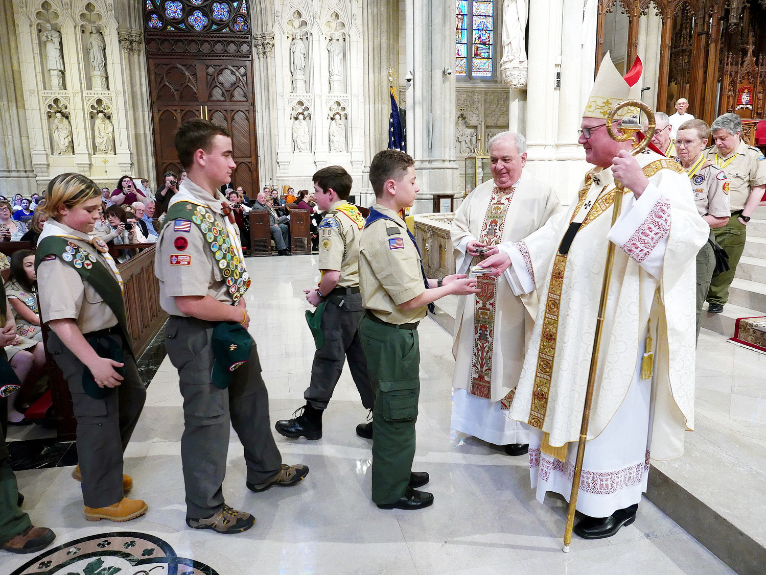 Cardinal Dolan presents medals to the scouts with assistance from Msgr. Anthony Marchitelli, scouting chaplain.