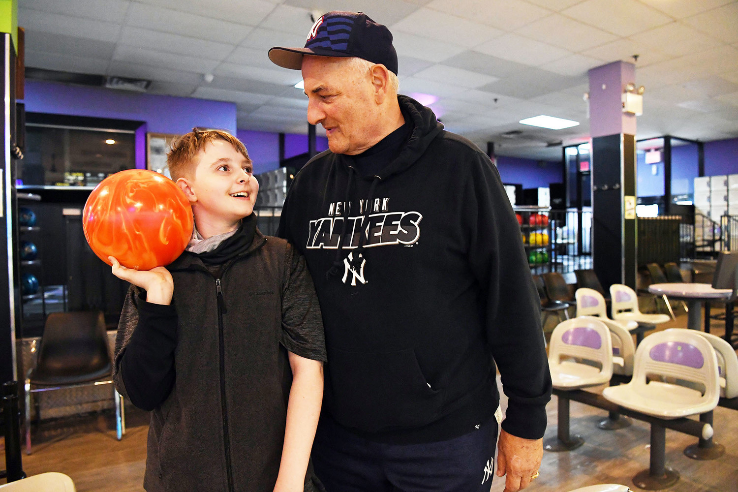 Jack Harkin, a sixth-grader at Intermediate School 24 on Staten Island, smiles with his grandfather Larry Ambrosino at Rab's Country Lanes April 17. Harkin, who started bowling last year, looks forward to spending time with his grandfather each Tuesday as he competes in the Staten Island CYO bowling league.