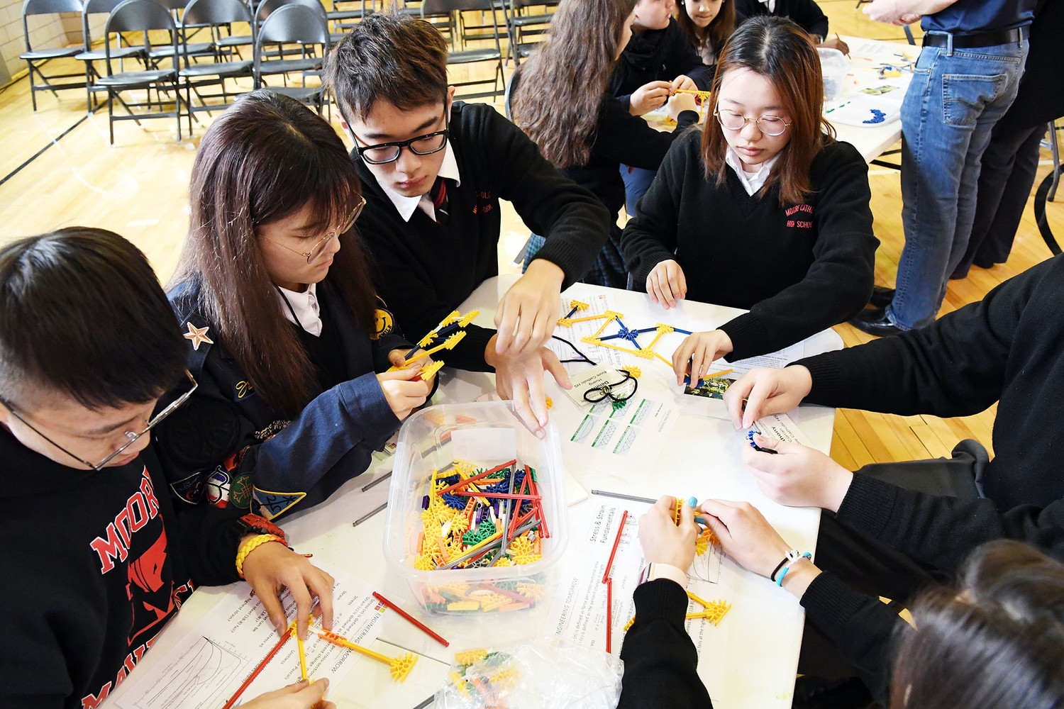 Moore Catholic students concentrate on their bridge experiment. From left: Jason Zhou, Rachel Zhang, Dennis Huang and Eunice Wang.