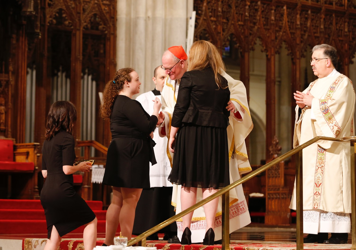 Cardinal Dolan receives the offertory gifts from gift bearers Myra Bowyer, Caitlin Whitehead and Aislinn Whitehead at the Memorial Mass in St. Patrick's Cathedral April 25.