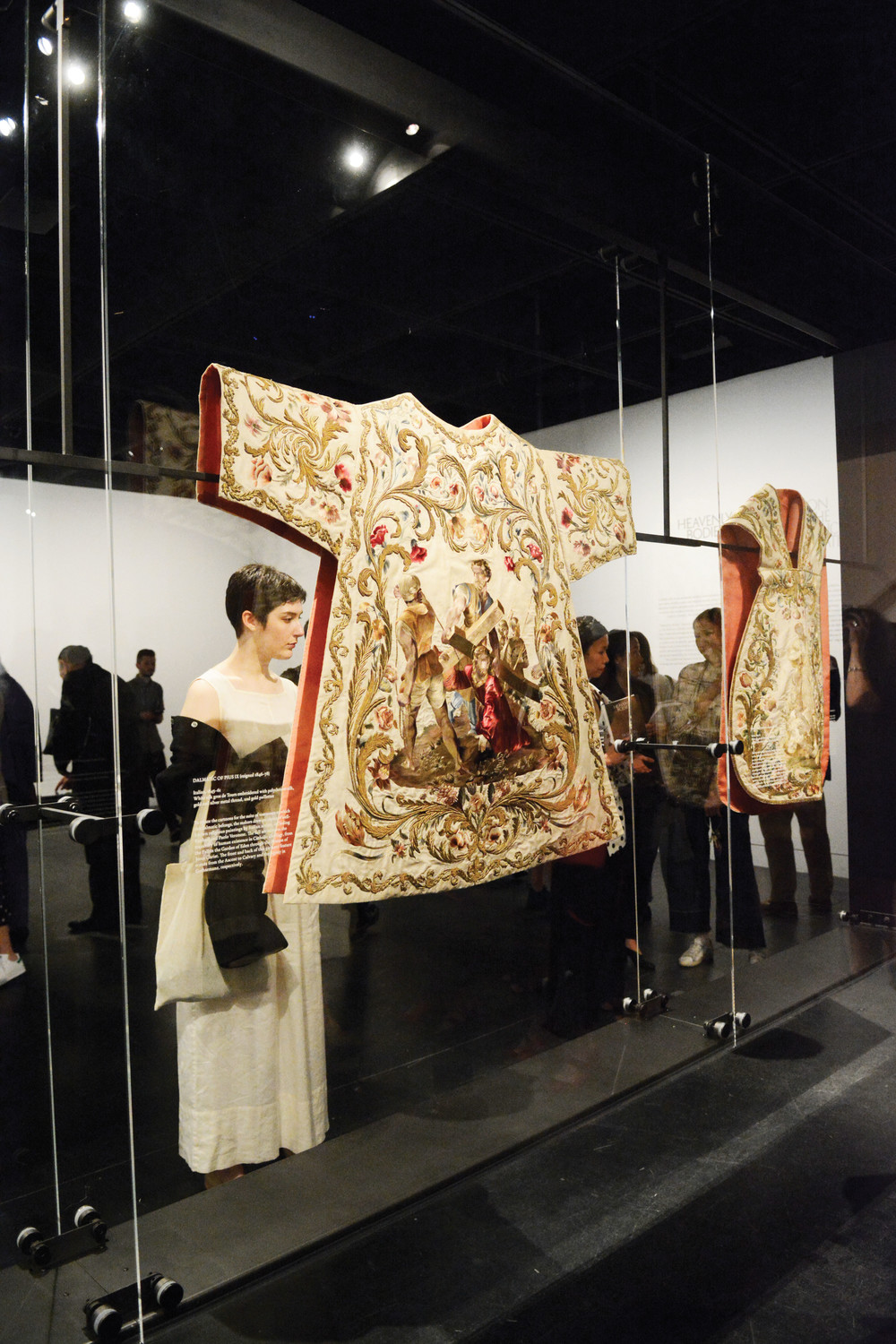 "During the press preview for ""Heavenly Bodies: Fashion and the Catholic Imagination"" at the Metropolitan Museum of Art May 7, a visitor, top left, inspects a dalmatic of Pope Pius IX, who was pontiff from 1846 to 1878."
