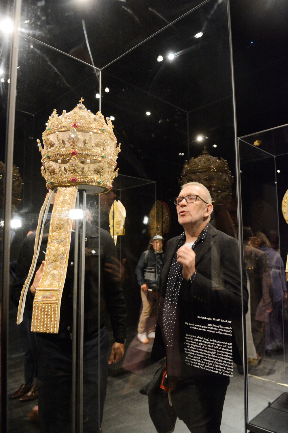 Fashion designer Jean-Paul Gaultier examines a papal tiara of Pius IX, a gift from Queen Isabella II of Spain that features 19,000 precious stones, the majority diamonds.