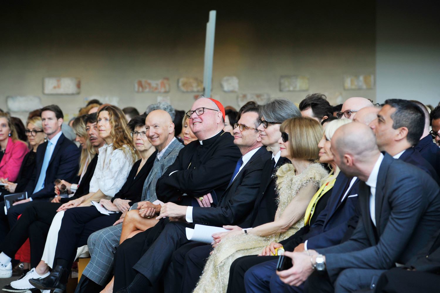 Cardinal Dolan sits in the front row with Christine Schwarzman, to his left, co-chair of the exhibit along with her husband, Stephen A. Schwarzman. To the cardinal's right were Dr. Daniel H. Weiss, president and CEO of the Metropolitan Museum of Art; Andrew Bolton, curator in charge, the Costume Institute; Anna Wintour, editor-in-chief of Vogue magazine; and Donatella Versace, a fashion designer.