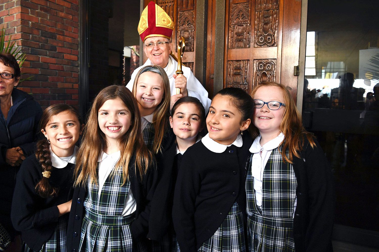 uxiliary Bishop John O'Hara gathers with students of Our Lady of Good Counsel School on Staten Island after celebrating the 50th anniversary of the first Mass in Good Counsel's present church on April 29.