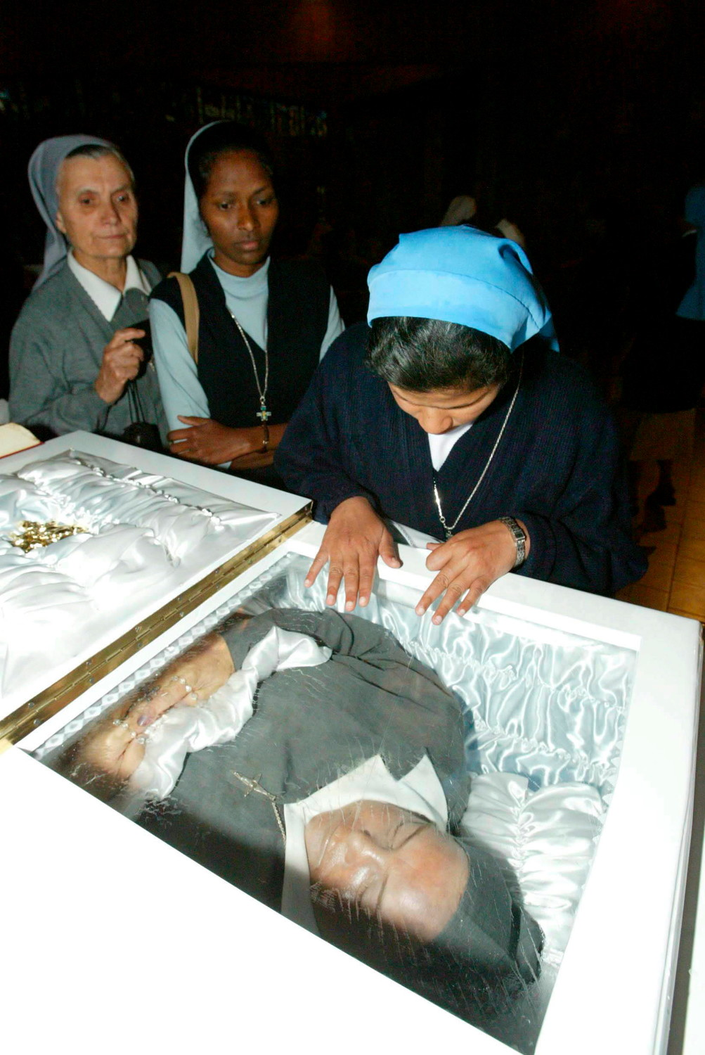 A woman religious prays over the body of Consolata Sister Leonella Sgorbati during her 2006 Funeral Mass in Nairobi, Kenya. Sister Sgorbati and her bodyguard were gunned down as they left the children's hospital where she worked in Mogadishu, Somalia. She will be beatified in Piacenza, Italy, May 26.