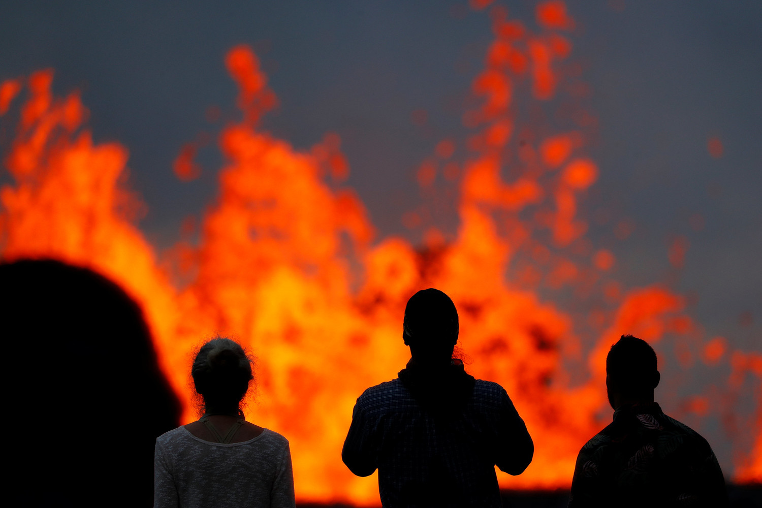 Onlookers stand on a lava flow to watch the Kilauea Volcano May 26 in the Leilani Estates near Pahoa, Hawaii. Hawaii County officials are alerting more residents in the Leilani Estates subdivision to flee fast-moving lava from Kilauea volcano. As of May 29, lava has destroyed 82 structures, including 37 homes.