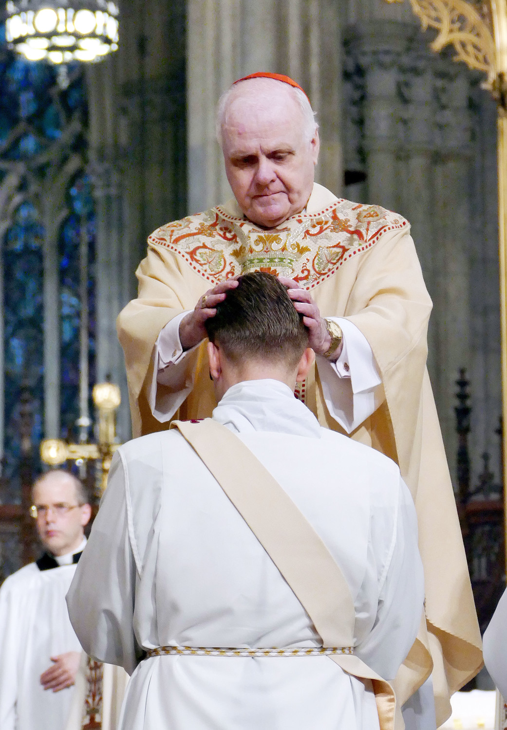 Cardinal Edwin O'Brien, the grand master of the Equestrian Order of the Holy Sepulchre of Jerusalem who was ordained for the Archdiocese of New York at St. Patrick's Cathedral in 1965, lays hands on one of the ordinands.