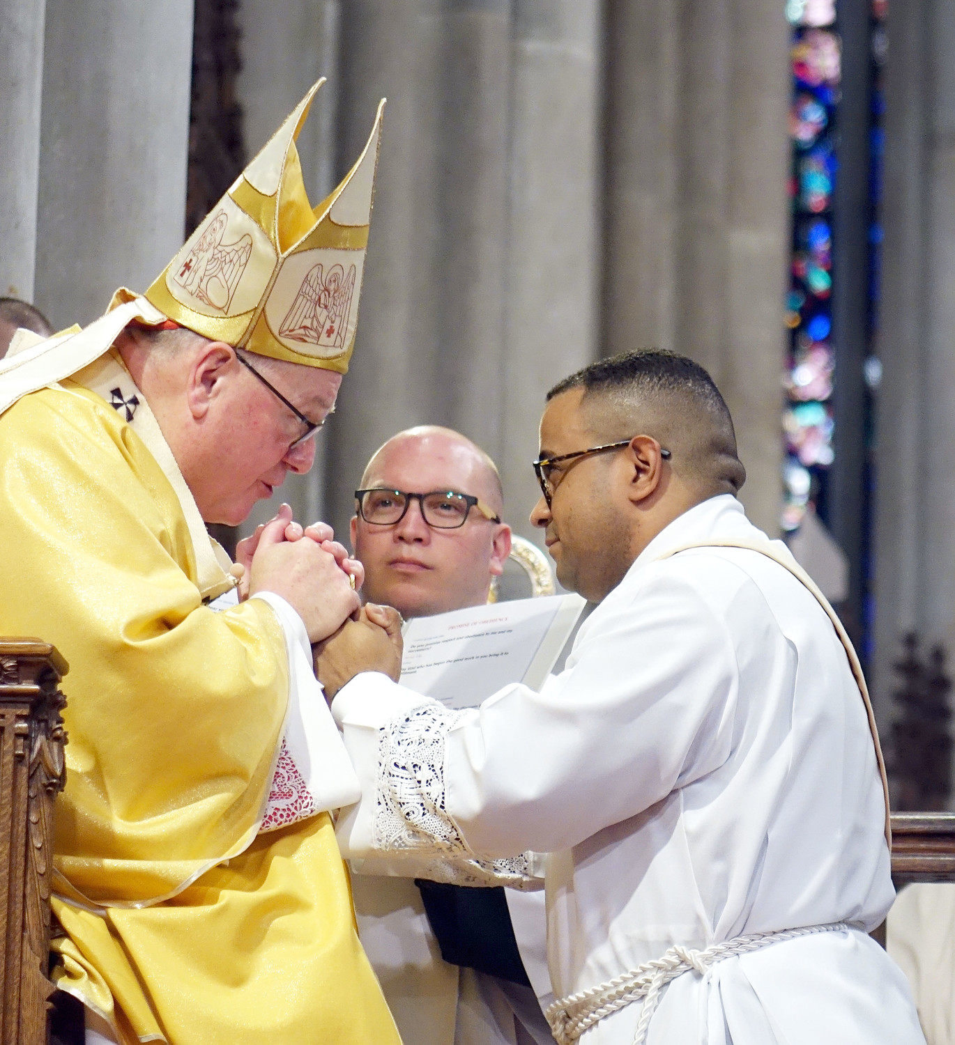 The cardinal clasps the hands of Father Osvaldo Hernandez during the Rite of Ordination.