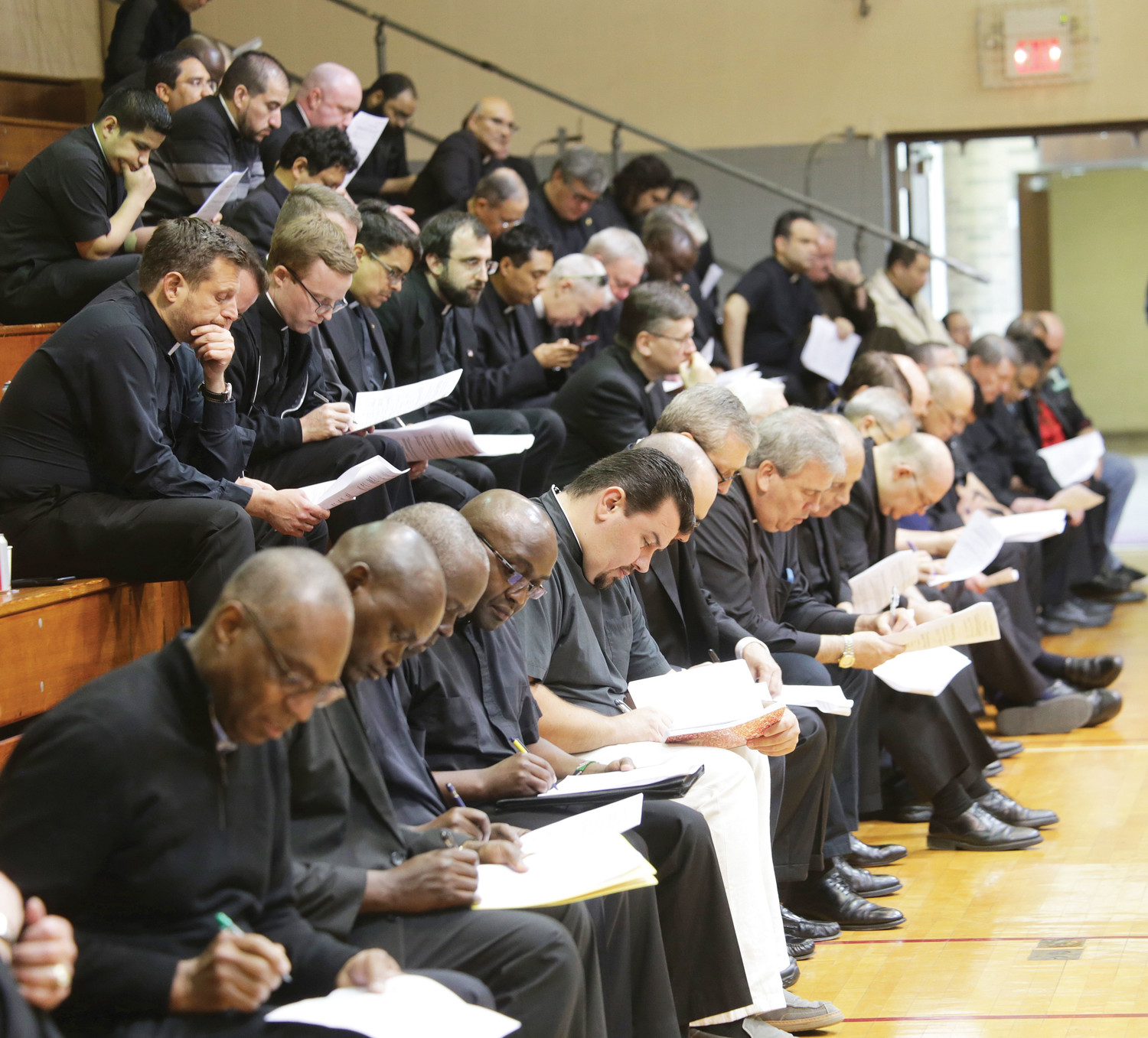 "PASTOR TO PASTORS—New York priests take careful notes on handout materials during the second session of the Safe Environment Convocation, at which Pastor Rick Warren spoke on ""Maintaining the Moral Integrity of the Ministry to Which God Has Called Us."" Nearly 800 priests heard the Evangelical pastor June 6-7 at Cardinal Spellman Center at St. Joseph's Seminary in Dunwoodie."