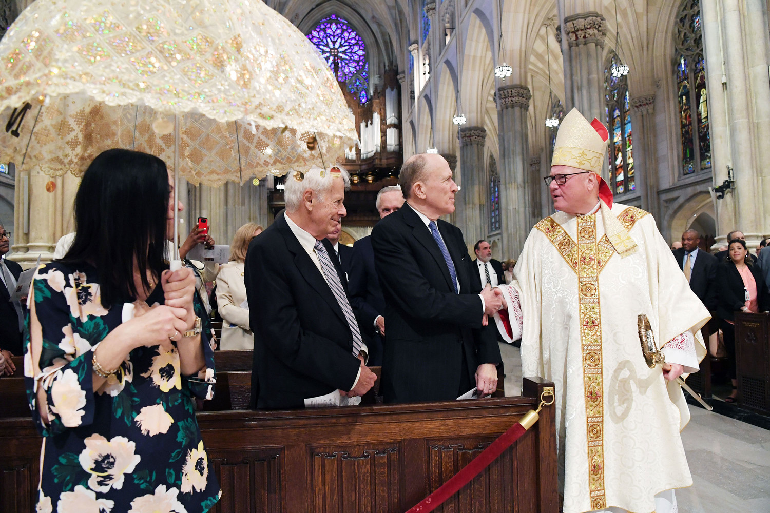 Cardinal Dolan greets Frank Serbaroli, chairman of ArchCare's board of trustees, and Dr. Karl Adler, M.D., vice chairman. At left, one of many decorative umbrellas, symbols of regality and respect for God and the Blessed Mother, is held aloft.