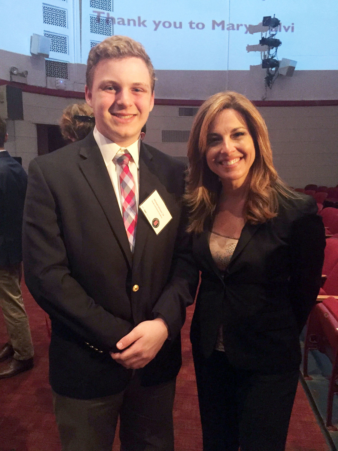 Stepinac Honors Academy student Michael Schwarz greets broadcast journalist Mary Calvi, who served as moderator of the Clean Water Solution Symposium at Archbishop Stepinac High School in White Plains May 30.
