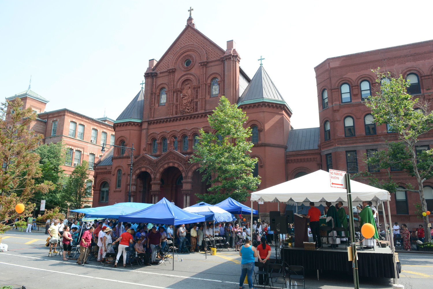 The church makes for a majestic backdrop in this overview of the afternoon street Mass on East 106th Street.