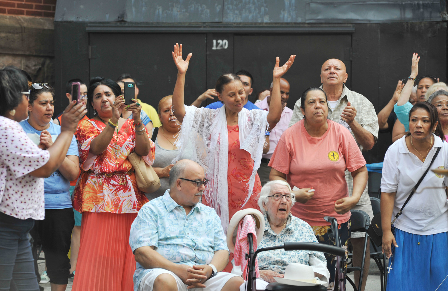 Emilio Rodriguez, 76, and his 103-year-old mother, Justa Rodriguez, both seated, join in the celebration of the Sunday street Mass outside St. Cecilia and Holy Agony Church in Manhattan July 1.