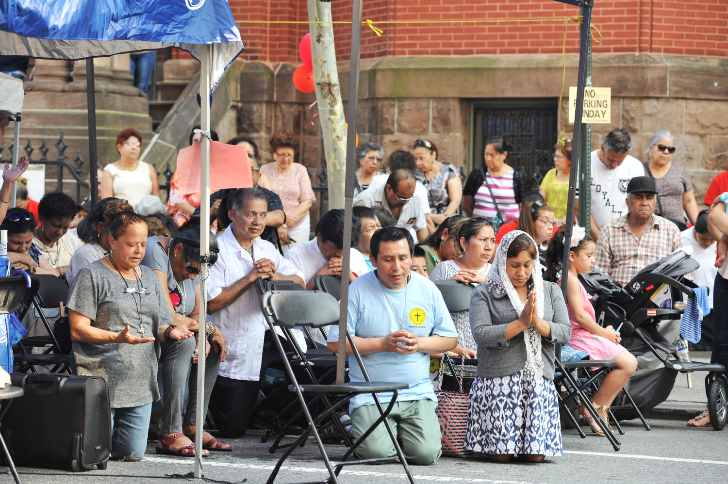 The sun shines brightly upon congregants as they pray during the street Mass outside St. Cecilia and Holy Agony Church on East 106th Street in Manhattan July 1. Father Peter Mushi, A.J., the pastor, served as principal celebrant and homilist.