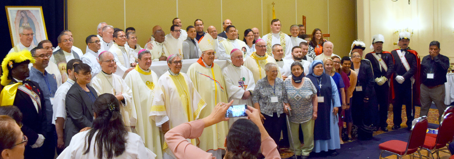 Bishops and clergy from the eight Catholic dioceses in New York state gather with the Region 2 Encuentro leaders and the consultative team following the closing Mass of the June 22-24 Region 2 V Encuentro at the Desmond Hotel in Albany. At the center is Bishop Nicholas DiMarzio, the principal celebrant of the Mass.