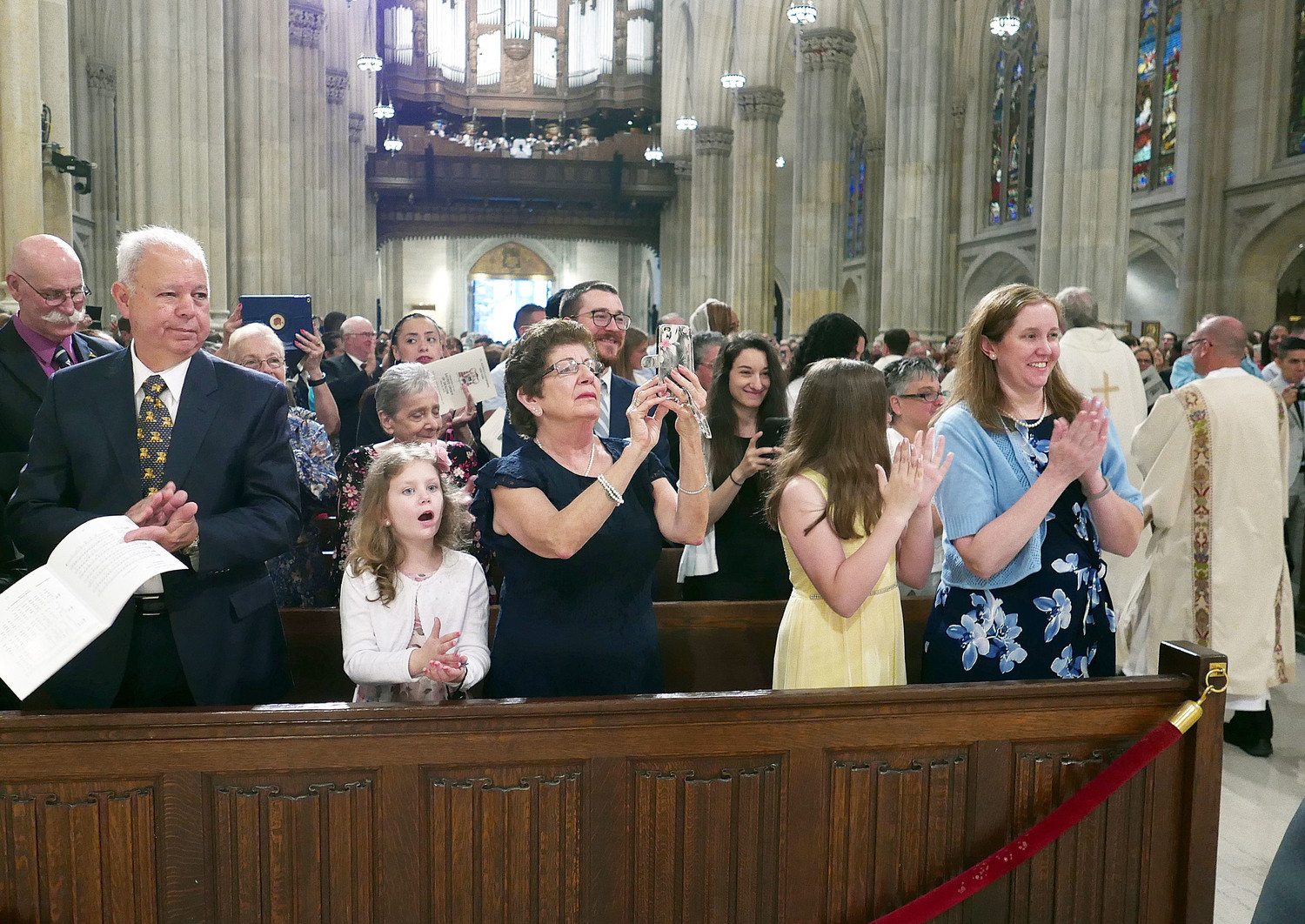amilies join in applause as the new deacons recess at the end of Mass. Those in the front pew include Kerri Bennett, right, wife of Deacon Thomas Bennett, and their daughters, Abby and Molly.