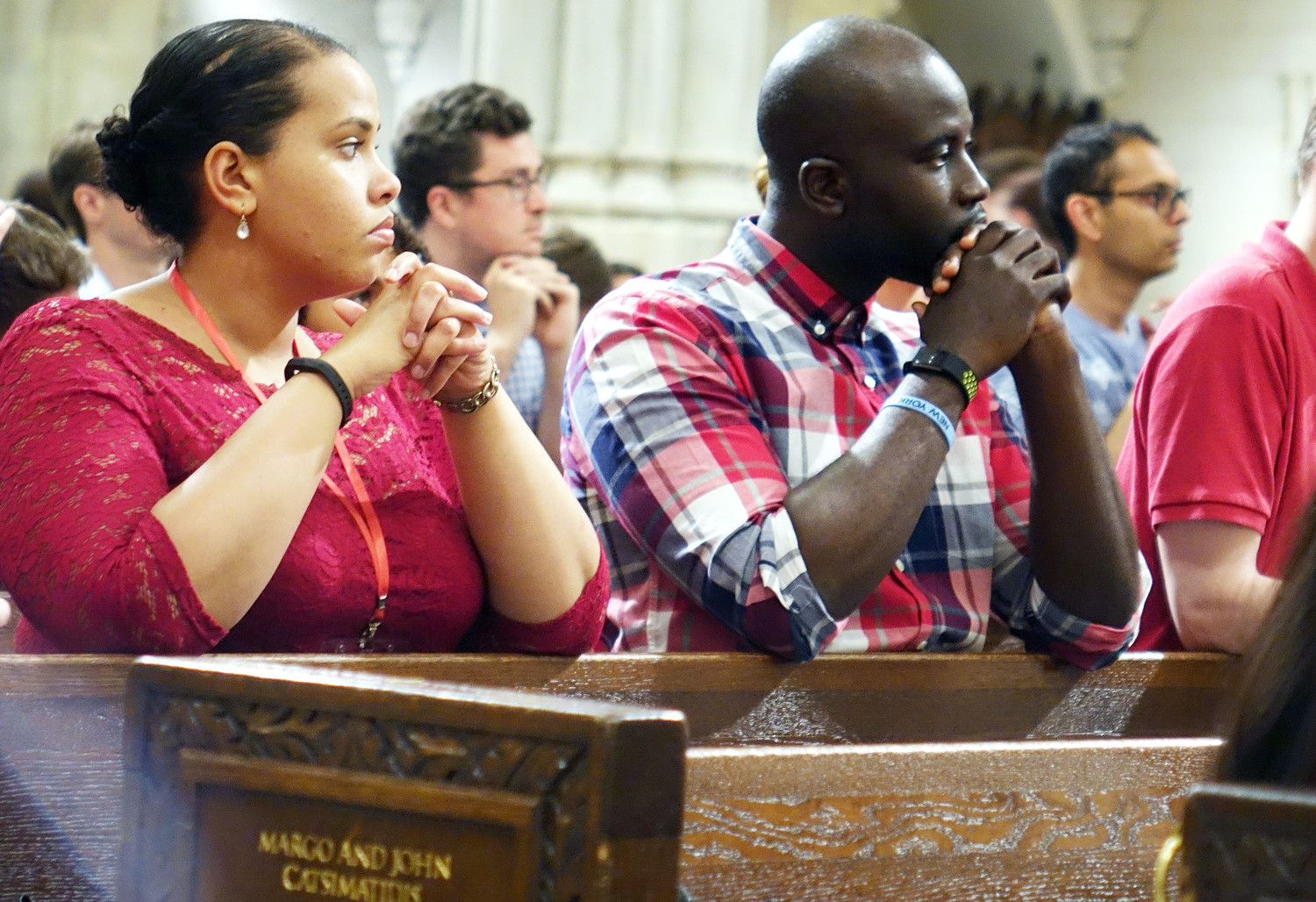 Marcia Correa and Fidelis Idoko kneel during the Liturgy of the Eucharist. T
