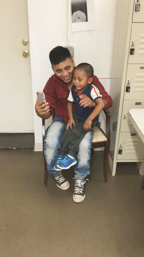 Adan, 26, and his son Juan, 4, share a FaceTime call from a Bronx Catholic Charities agency with family in Guatemala.