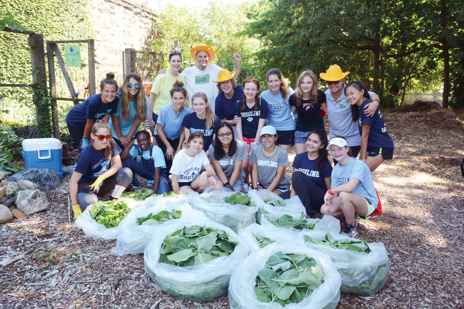 Fifteen students from The Ursuline School in New Rochelle, joined by their new principal, Rosemary Beirne, navy blue shirt and golden hat, reap what they sowed at the Food for Others Garden in the Wakefield section of the Bronx July 10. Students filled bags with collard greens, basil and jalapeno peppers.