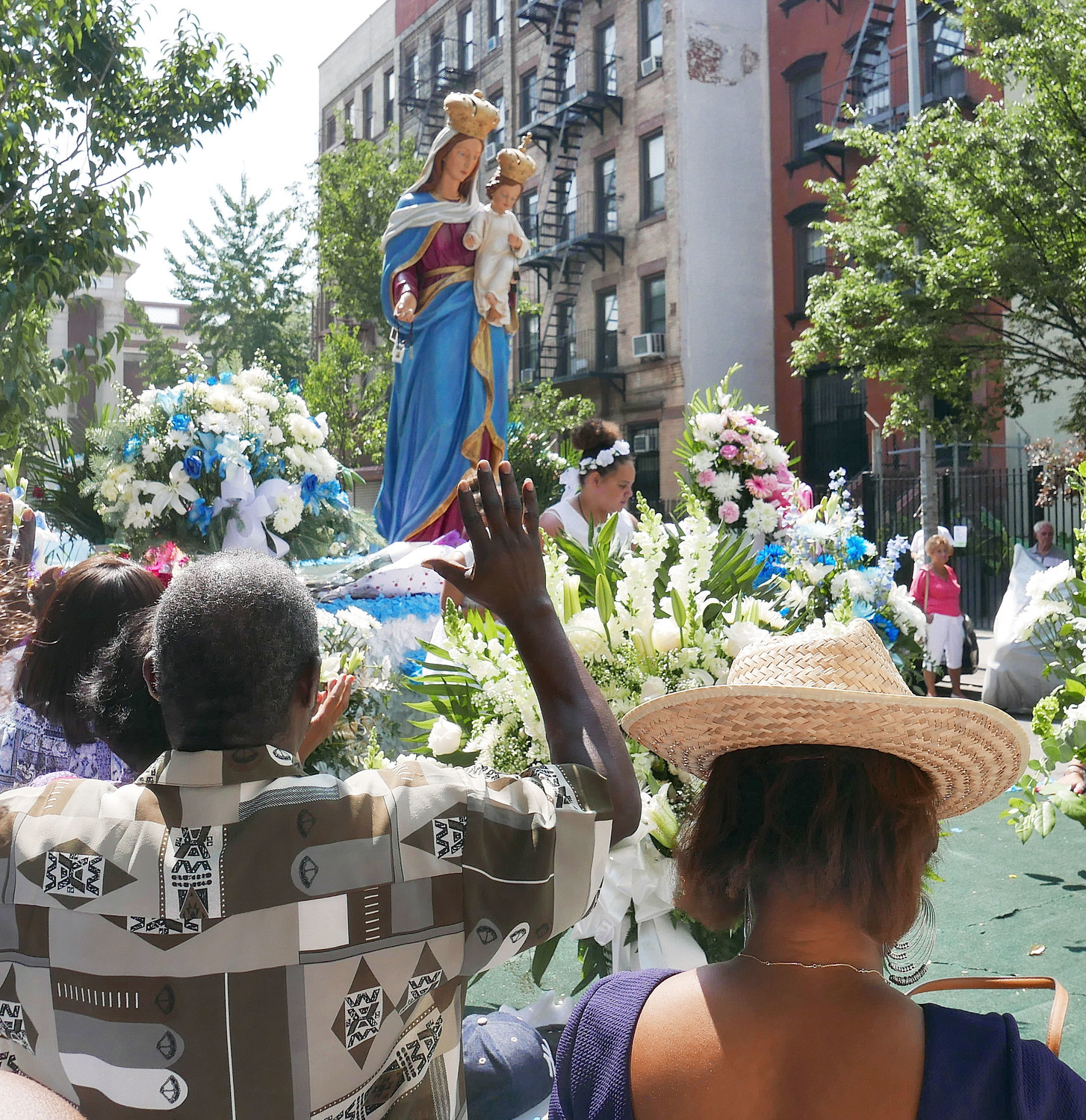 People acknowledge the statue of Our Lady of Mount Carmel during the street procession in East Harlem following the solemn Mass.