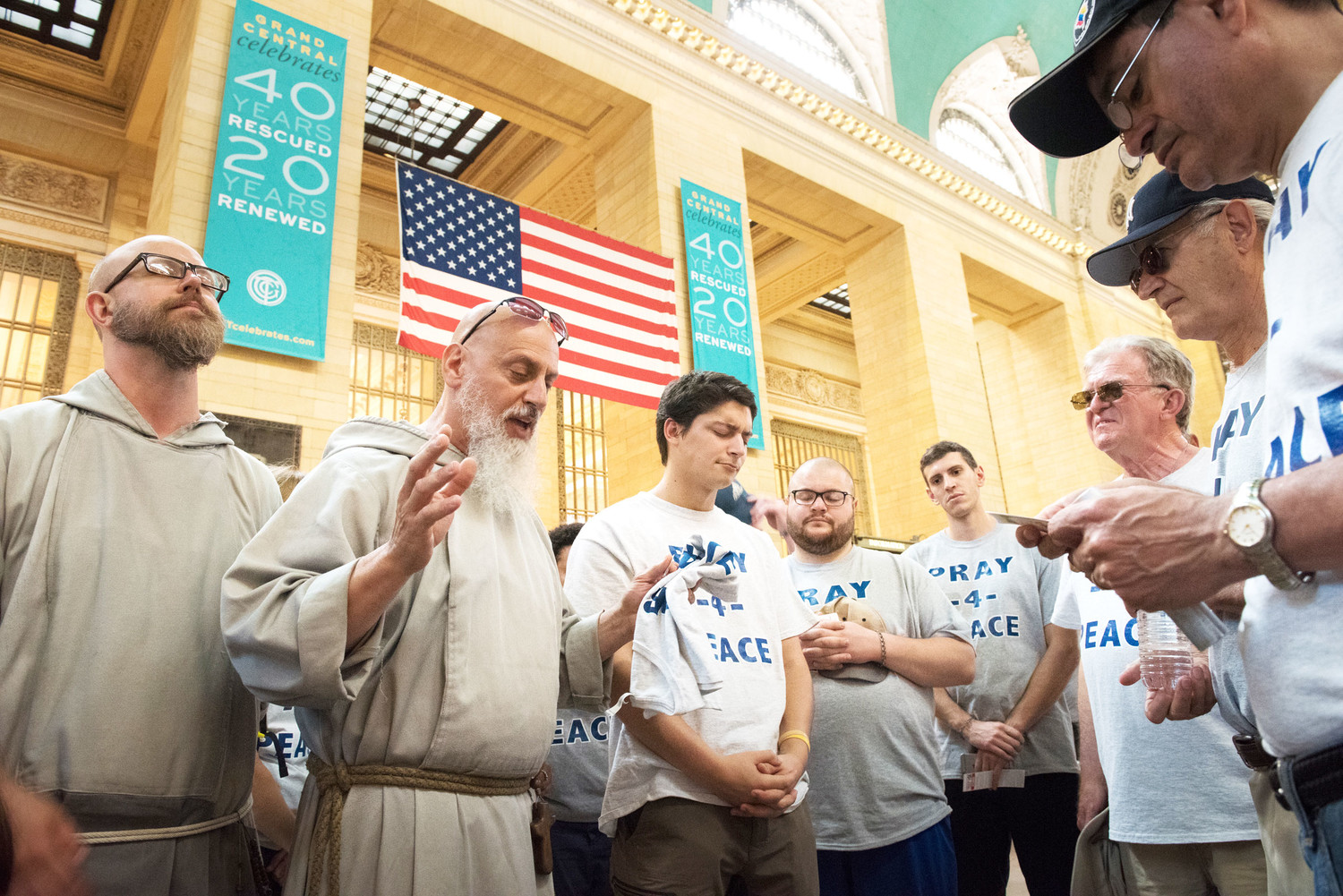 Father Louis Leonelli, C.F.R., second from left, leads a prayer gathering inside Grand Central Station in Manhattan. More than 50 people participated in a Pray for Peace walk to Yankee Stadium in the Bronx June 30, a very hot Saturday when the Yankees hosted the Boston Red Sox. The event organizer, Al Forte, 75, with sunglasses, is third from right.