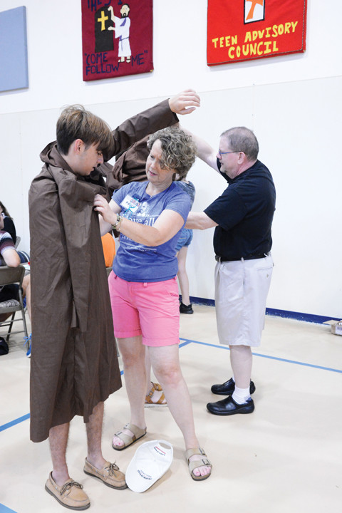 "BLESSED SOLANUS ON STAGE—Cast member Nate Rosengrant, 16, tries on his costume with assistance from Paula Stuckart in St. Genesius Gymnasium at the Capuchin Youth & Family Ministries campus in Garrison July 30. The teen from Middletown, Conn., is one of 23 young people performing Friday, Aug. 3, in ""Solanus: Blessed in America, The Story of Blessed Solanus Casey, O.F.M. Cap."" as part of the six-day Catholic Literature & Arts Summer Program overnight retreat."
